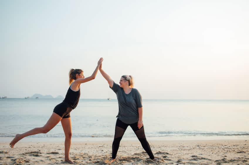 Zwei Frauen haben am Strand Sport gemacht und klatschen sich nun ab. Im Hinterfgrund liegt das weite Meer.