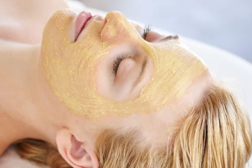 Eine Frau mit blonden Haaren liegt mit geschloßenen Augen auf einer Liege. Sie trägt eine gelbliche Gesichtsmaske.