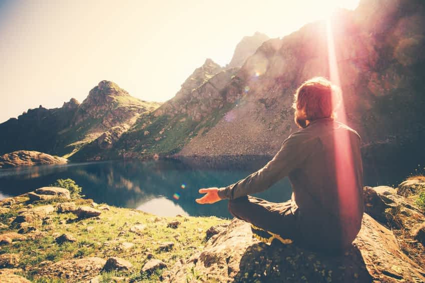 Bärtiger Mann beim entspannten Yoga an einem Bergsee