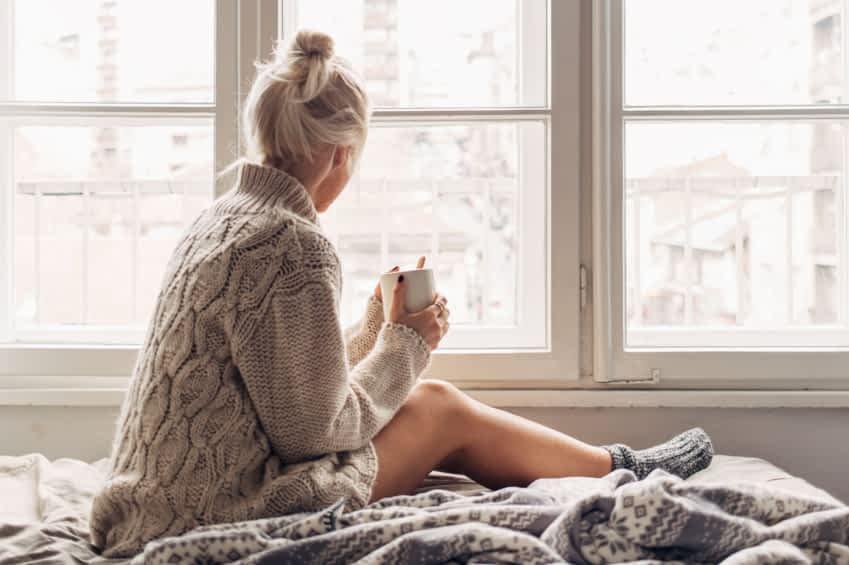 Eine junge Frau sitzt auf ihrem Bett und hält mit beiden Händen eine Tasse Tee. Sie trägt eine Wolljacke und gestrickte Socken. Sie schaut aus dem Fenster.