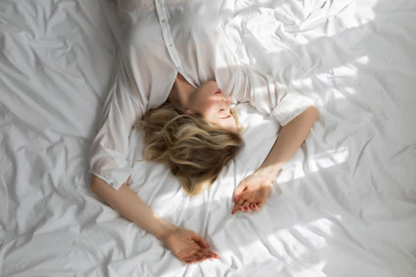 Das Bild zeigt eine schlafende Frau im Bett am Morgen. Durch das Fenster fallen Sonnenstrahlen auf sie.