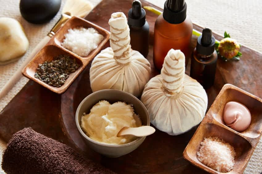 Auf dem Bild sind biologische Zutaten für eine ayurvedische Spa-Behandlung abgebildet. Darunter Kräuterpackungen, ein Aromatherapie-Peeling, Massageöl, Salz, Lavendel und verschiedene Lotionen.