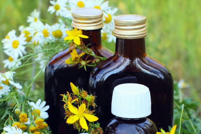 Das Bild zeigt medizinische Kräuteröle und eine Trinktur in Glasflaschen.