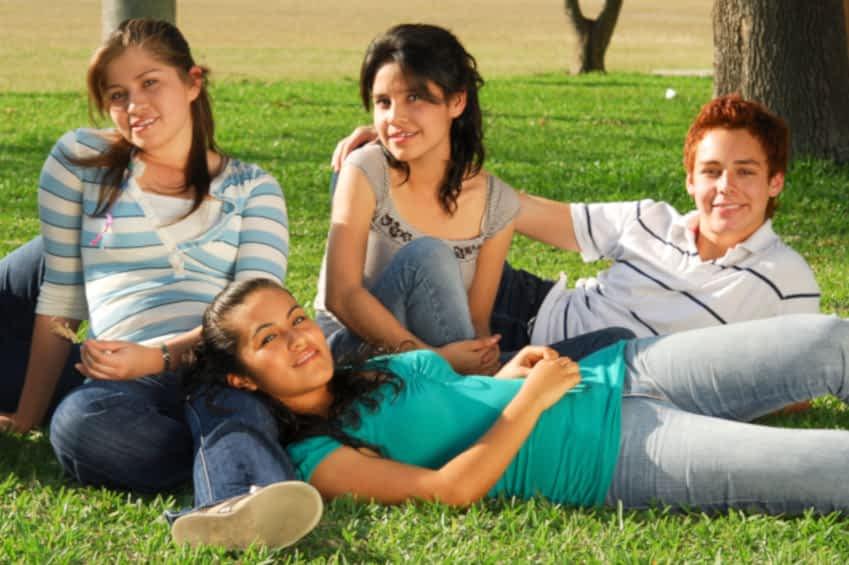 Man sieht eine Gruppe Jugendliche auf einer Wiese. Zwei Mädchen mit schulterlangen dunklen Haaren sitzen im Gras, ein Junge liegt daneben und hat den Arm um das eine Mädchen gelegt und im Vordergrund liegt ein Mädchen mit dem Kopf auf dem Bein der anderen. Sie wirken glücklich und die Sonne scheint.
