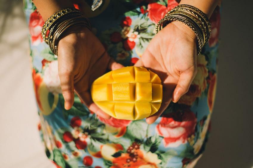 Eine Frau mit einem bunten Gewand und vielen Armreifen hält eine perfekt geschnittene Mango in die Kamera.