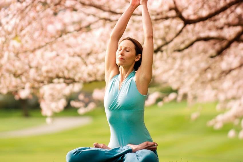 Frau im Lotussitz unter einem Kirschbaum mit zum Himmel ausgestreckten Armen.