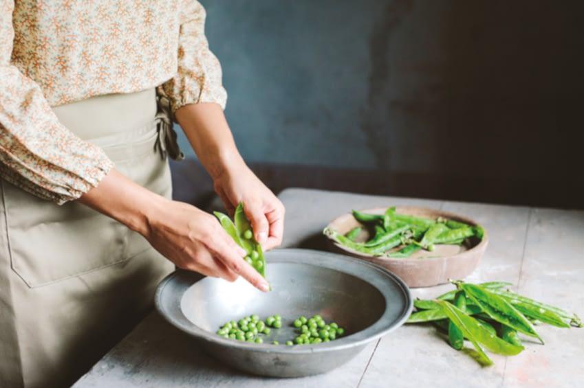 Man sieht eine Frau mit gemusterter Bluse an einem Tisch stehen. Sie pult Erbsen und trennt sie von ihrer Schale und sortiert sie dementsprechend auf verschiedenen Teller.