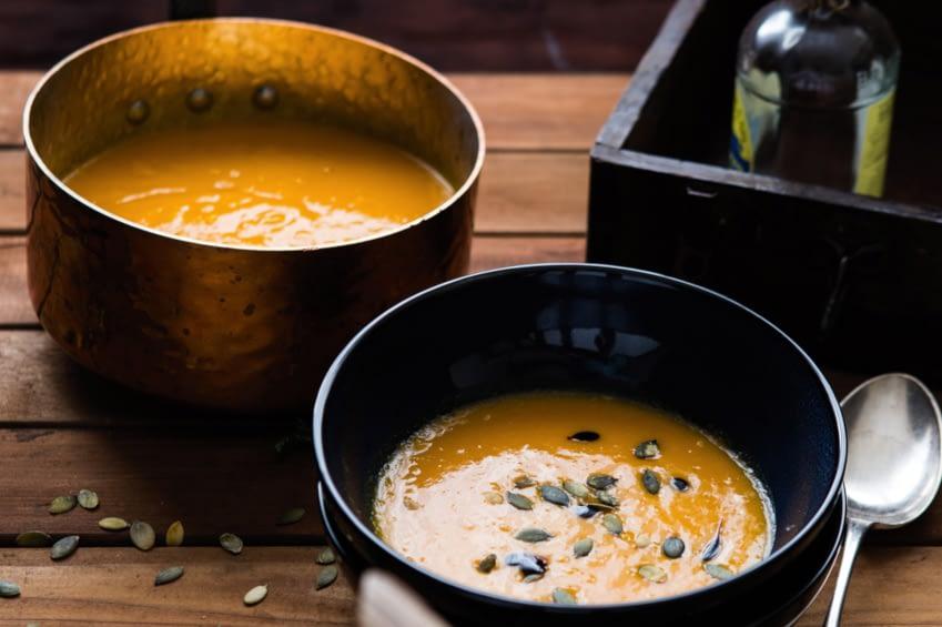 Hier erkennt man eine Schüssel und ein Topf mit einer köstlichen, orangenen Kürbissuppe, diese ist mit Kürbiskernen garniert. Ein Löffel liegt zum essen bereit.