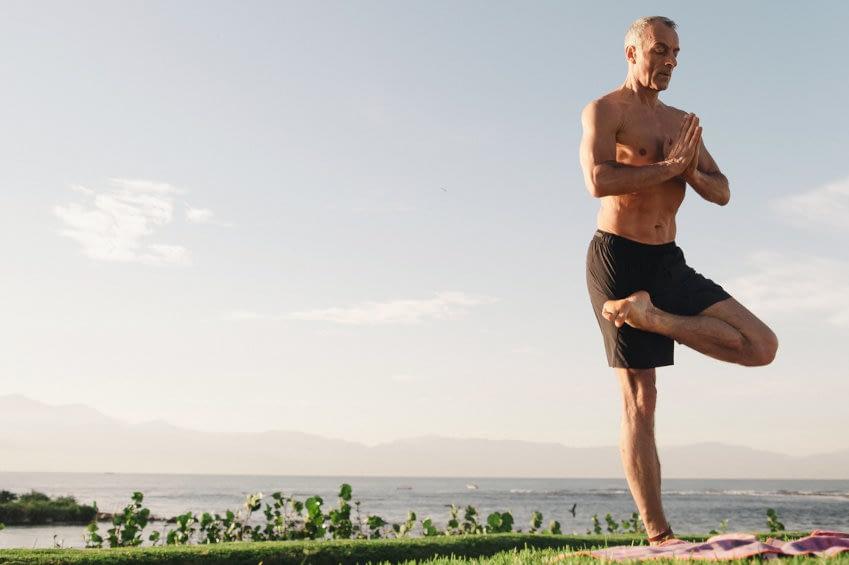 Muskelöser, fitter Senior macht Draußen-Yoga in der Morgensonne