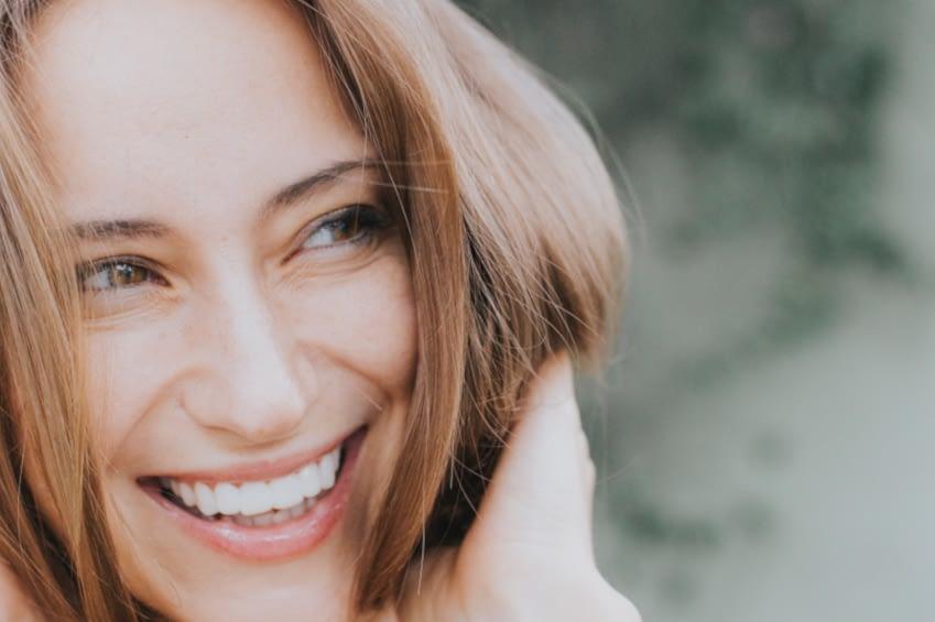 Eine junge Frau lächelt in die Ferne. Der Hintergrund ist unscharf.