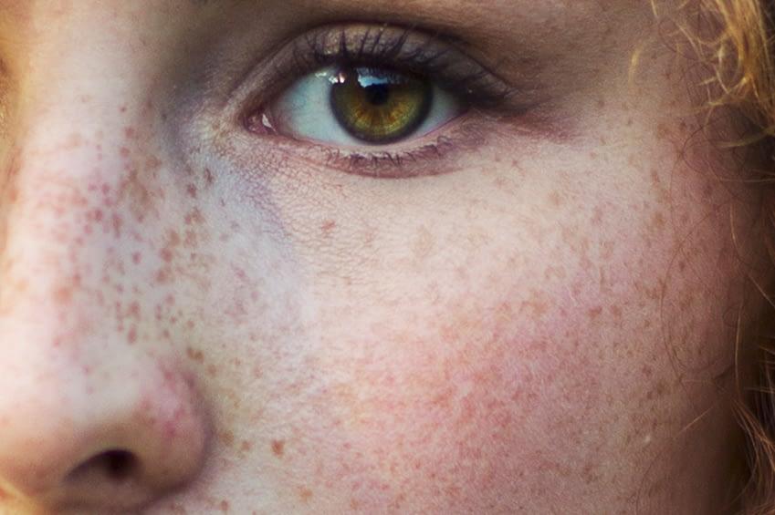 Man schaut einer jungen Frau in ihre grün, braunen Augen. Mehr als ihr linkes Auge, ein Teil der Nase, ihre Sommersprossen und ihr leicht gerötetes Gesicht.