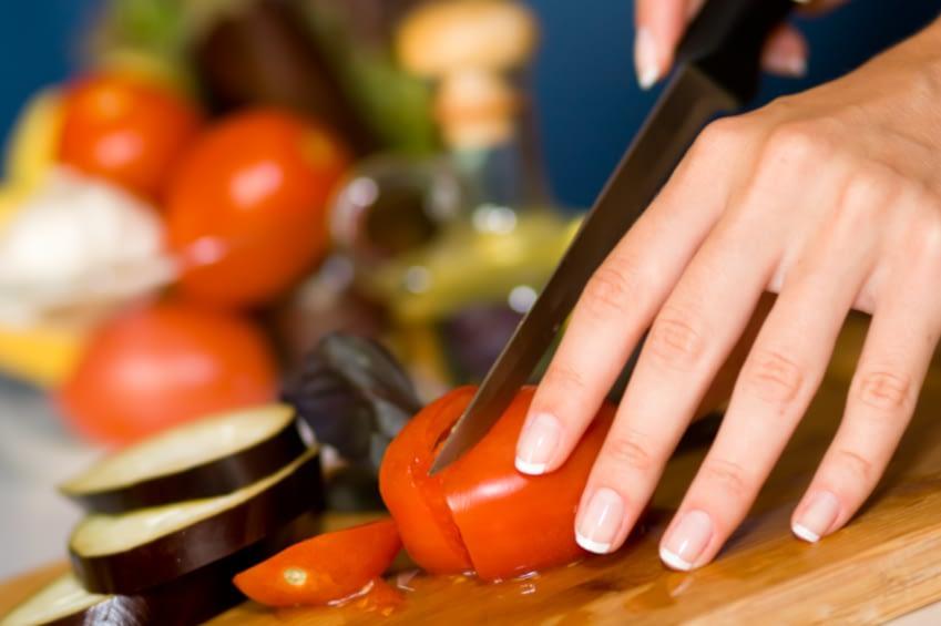 Man erkennt Frauenhände die eine Tomate halten und diese, sowie anderes Gemüse, auf eienm Holzbrett in Scheiben schneidet.
