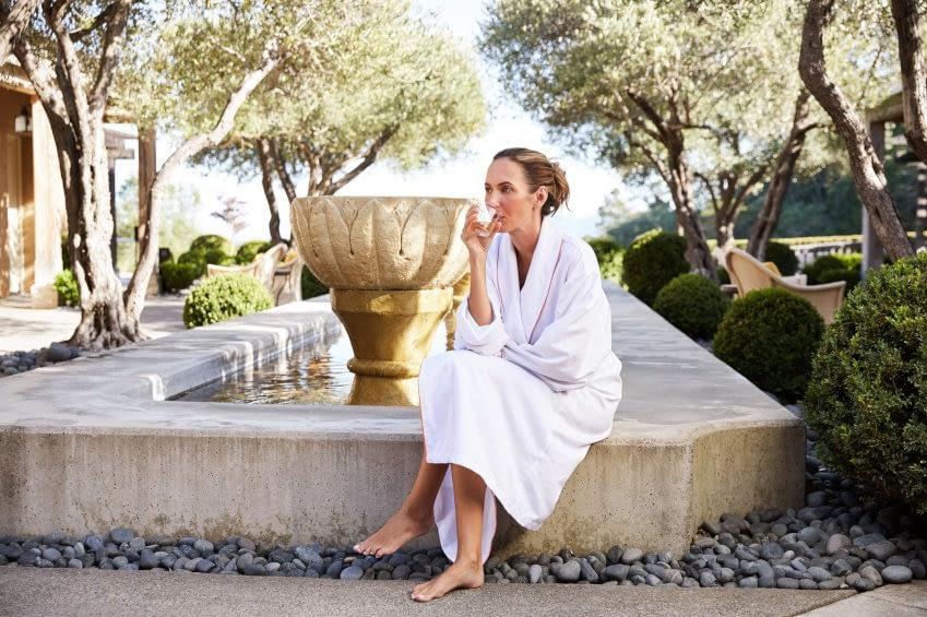 Das Bild zeigt eine Frau im Bademantel nach ihrem Kurprogramm. Sie genießt ein Glas Tee im Resort.