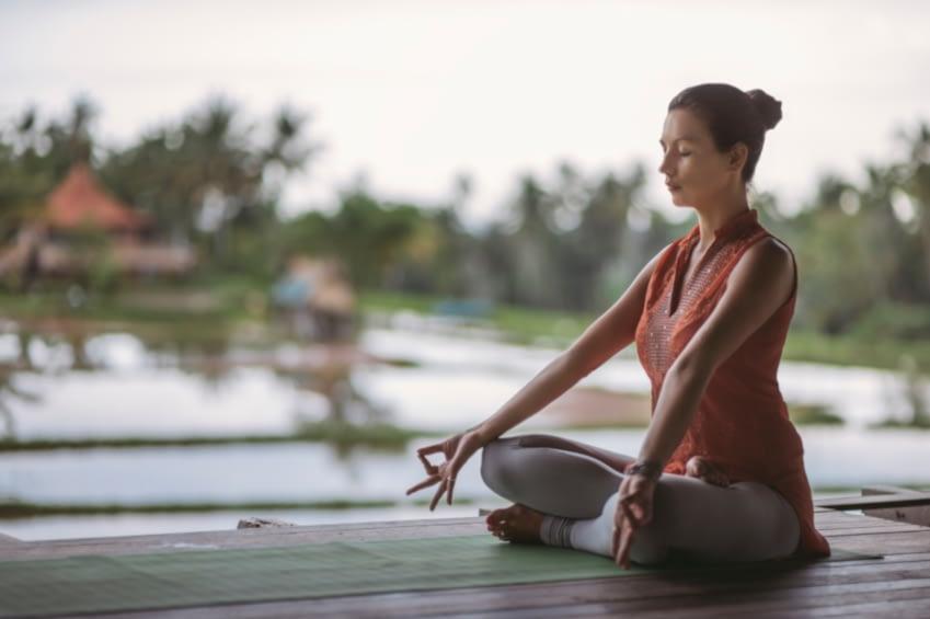 Eine junge Frau, mit braunem Dutt, Meditiert auf einer Yogamatte im Freien. Sie hat die Augen geschloßen und ihre Hände auf den Knien ausgestreckt. Im Hintergrund erkennt man unscharf eine Landschaft mit Bäumen, Wasser und entfernt steht ein Haus.