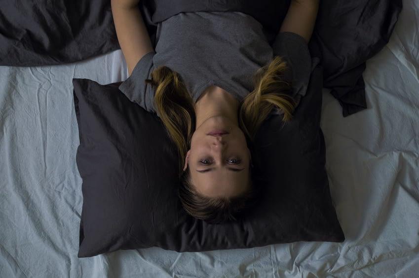 Eine junge Frau liegt im Bett auf dem Rücken und ist wach. Sie schaut direkt in die Kamera und trägt ein Shirt.