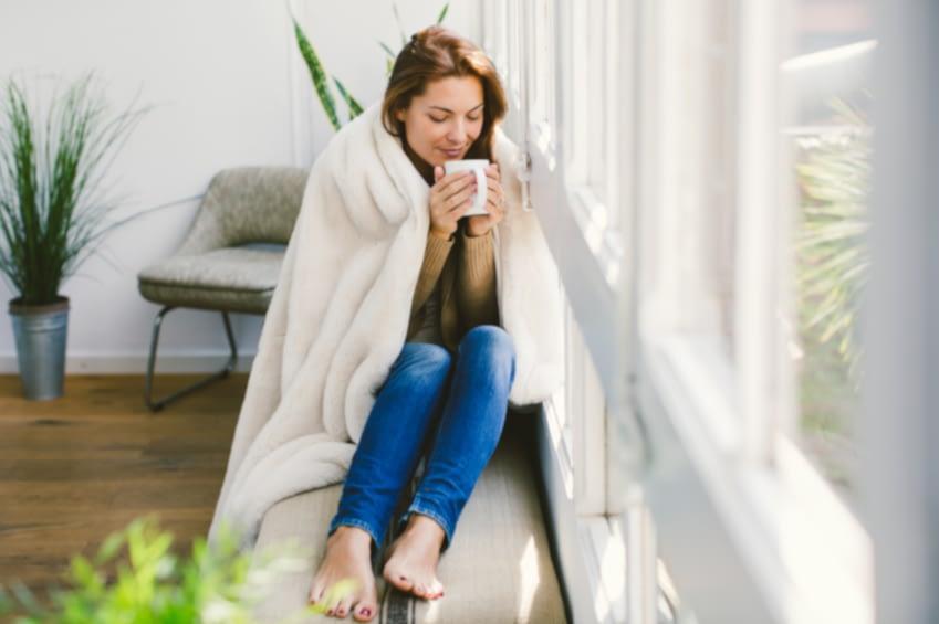 Eine junge Frau sitzt am Vormittag auf einer Bank vor ihrem Fenster in eine Decke gehüllt und trinkt eine frische Tasse Tee.
