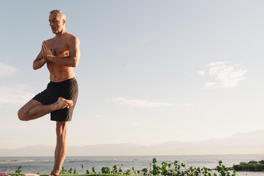 Auf dem Bild ist ein muskolöser, fitter, aber älterer Mann abgebildet. Er praktiziert Yoga im Freien. Er befindet sich in der Baum-Pose.