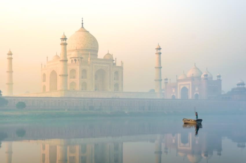 Man sieht da tatch mahal in Indien. Alles geht in eine Dunst unter und vor dem Tempel ist ein kleines Boot im Wasser, von dem aus jemand rudert.