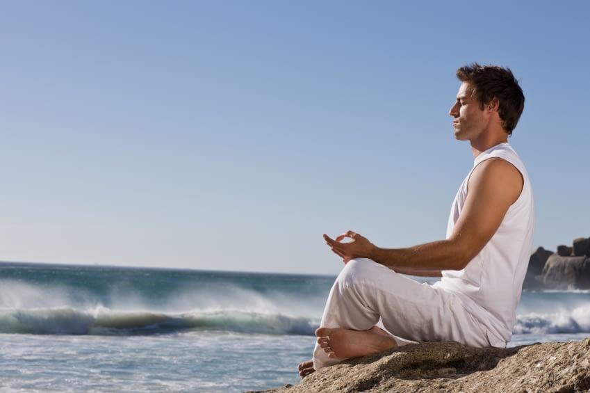 Ein junger Mann sitzt auf einem Felsen, der zum Meer gerichtet ist. Er hat die Augen geschloßen und sitzt in einer meditierdenden Haltung. Er trägt weiße Klamotten und hat kurze, braune Haare.