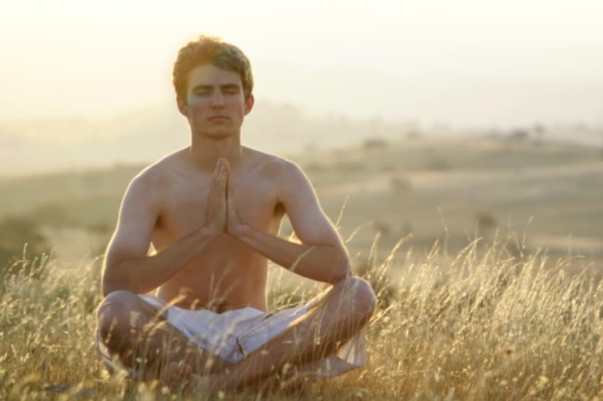 Ein junger Mann sitzt auf einer Wiese in der Natur. Er hat die Augen geschloßen und hält die Hände vor der Brust zusammen. Er Meditiert.