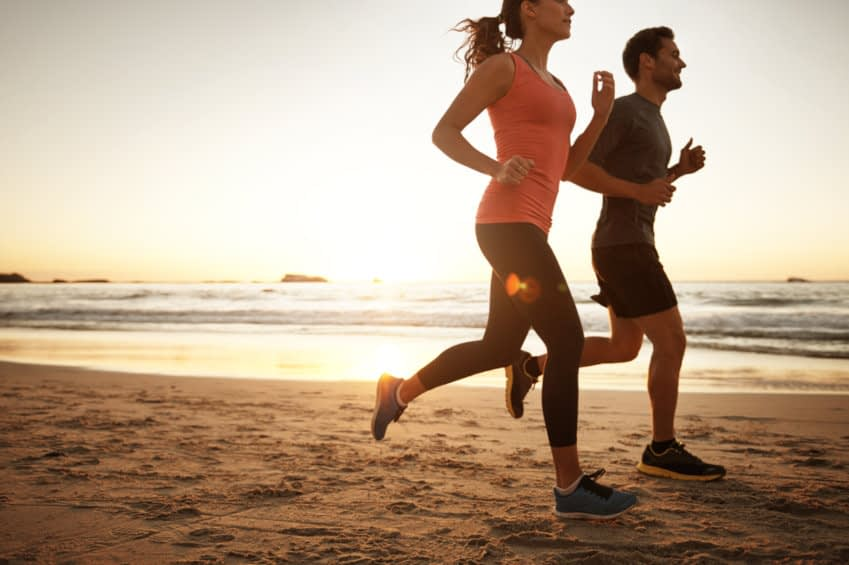 Das Foto zeigt eine Seitenaufnahme von einem Paar, dass am Strand joggt.