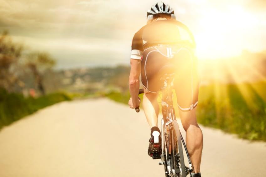 Zur Entschleunigung kann auch Beschleunigung gehören. Man sieht einen Mann, der auf einem Rennrad der Sonne entgegen fährt. Er trägt einen Helm und sportliche Kleidung.