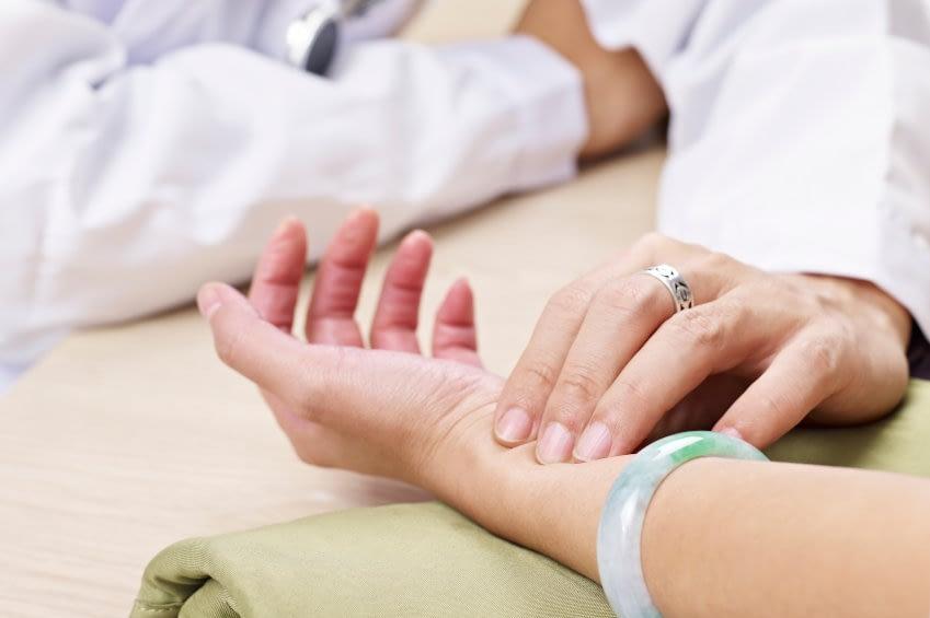 Das Bild zeigt einen Arzt bei der Pulsdiagnose an einer weiblichen Patientin.