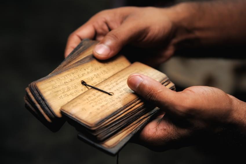 Zu sehen sind Schriften der Yogageschichte. Kleine Tafeln die mit einem Band in der mitte der Seite zusammengehalten werden.