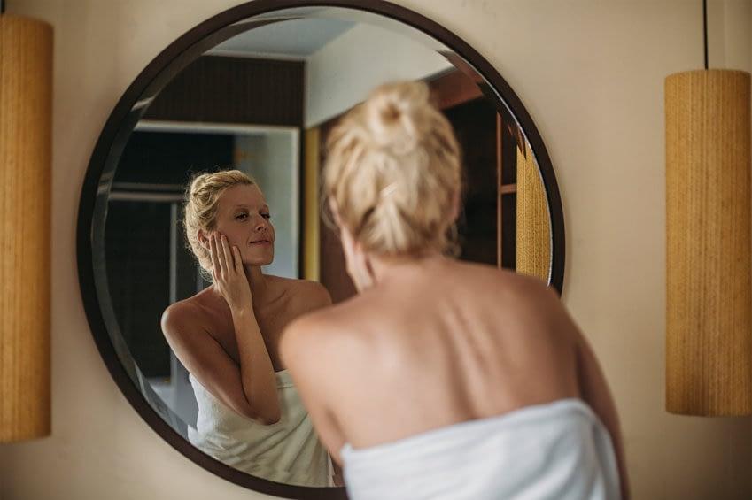 Eine Frau steht vor dem Spiegel und trägt eine Gesichtsmaske auf. Sie ist nur in einem Handtuch bekleidet und hat ihre Haare hochgebunden.