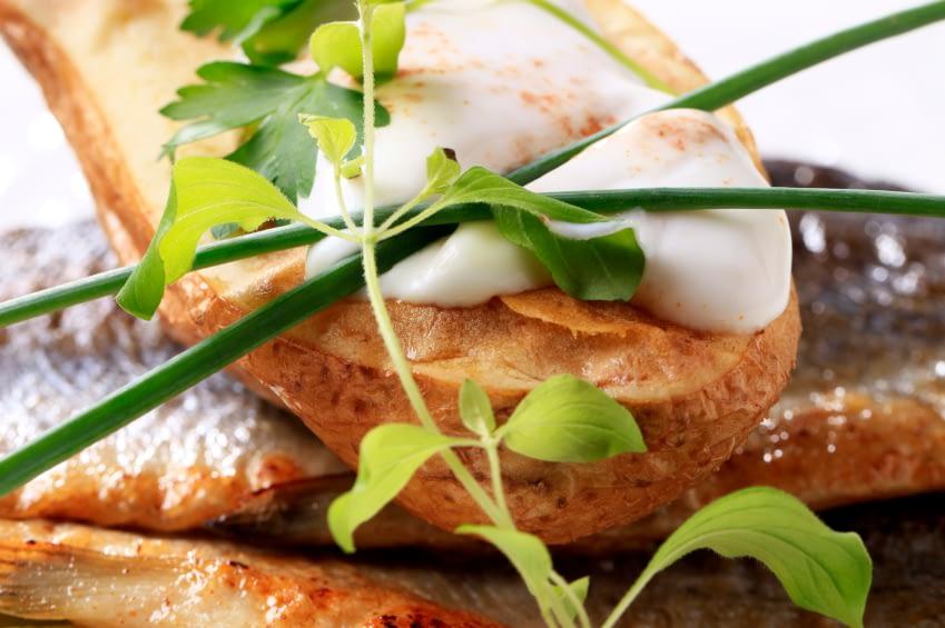 Man sieht eine Nahaufnahme eines Gerichts. Es gibt gebratenes Fleisch, daruf einen Löffel Dressig und garniert mit Schnittlauch und anderen Kräutern. Alles andere als Trennkost.